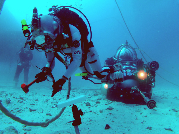 NASA astronaut Dottie Metcalf-Lindenburger tests ways to anchor to the surface of an asteroid on a simulated spacewalk on the ocean floor during the NEEMO 16 mission.