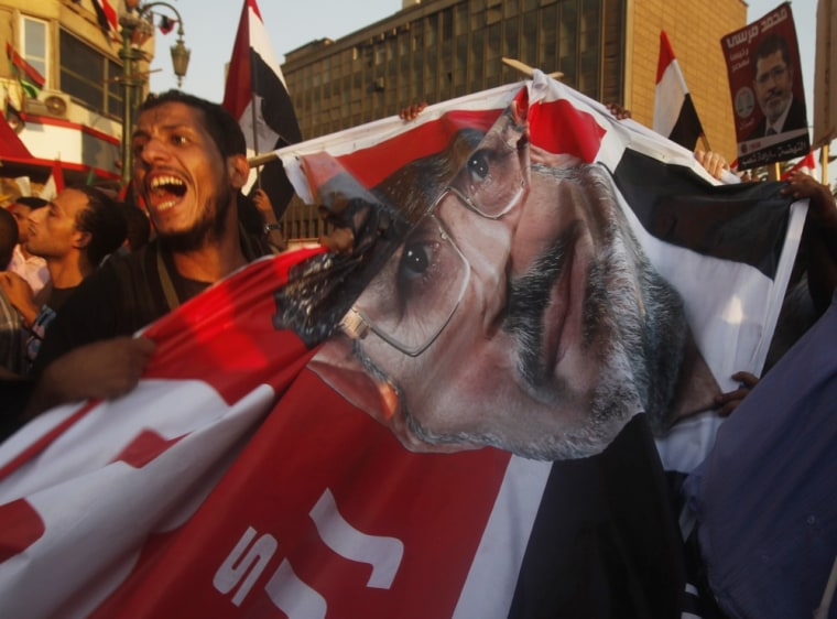 Image: Supporters of the Muslim Brotherhood's presidential candidate Mohamed Morsy carry a banner as they celebrate his victory in the presidential elections in Cairo