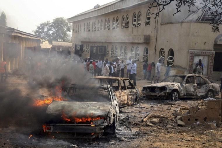 Image: A car burns at the scene of a bomb explosion at St. Theresa Catholic Church at Madalla