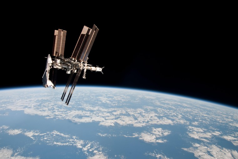 NASA's space shuttle Endeavour appears to hang off one end of the International Space Station in this photo taken by an astronaut aboard a nearby Soyuz spacecraft on May 23, 2011 during Endeavour's final mission. It is one of the first-ever images of a space shuttle docked at the space station.