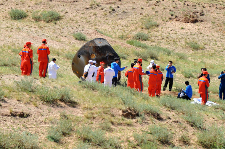 In this photo released by China's Xinhua News Agency, members of the search team approach the re-entry capsule of China's Shenzhou 9 spacecraft in Siziwang Banner of north China's Inner Mongolia Autonomous Region, June 29.
