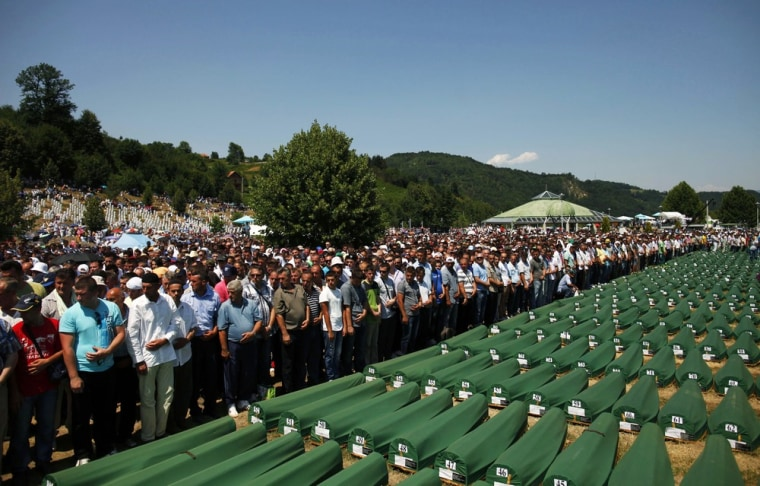 Image: Bosnian Muslims pray near coffins at the Memorial Center in Potocari during a mass burial, near Srebrenica