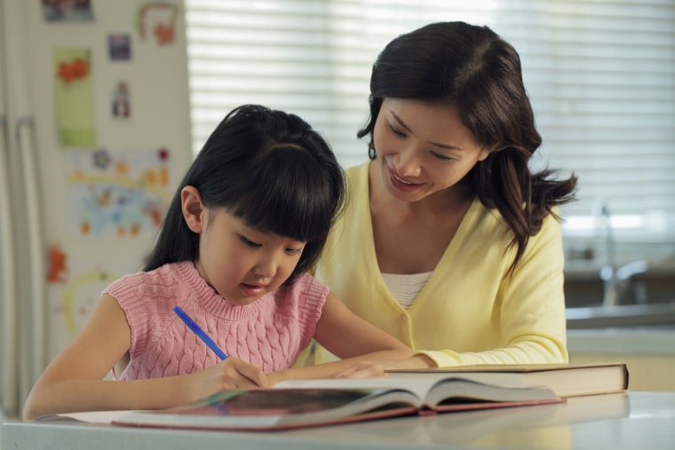 Image: A mother helps her daughter with homework