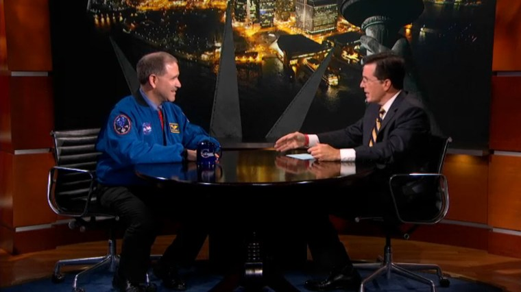 TV comedian Stephen Colbert discusses NASA's Mars rover Curiosity landing with astronaut John Grunsfeld, NASA's associate administrator for science missions, in this photo from a Comedy Central broadcast on Wednesday.
