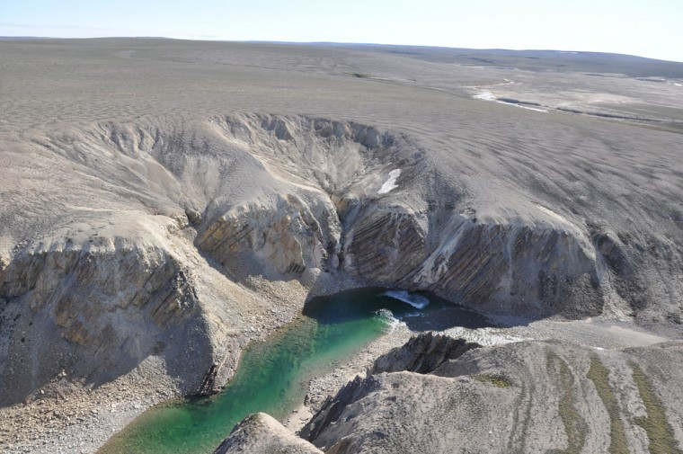 A river gorge cut into the tundra of northwestern Victoria Island shows steeply tilted sedimentary rock strata. These deformed beds represent the central uplift caused by rebound after the meteor impact that formed the Prince Albert crater.