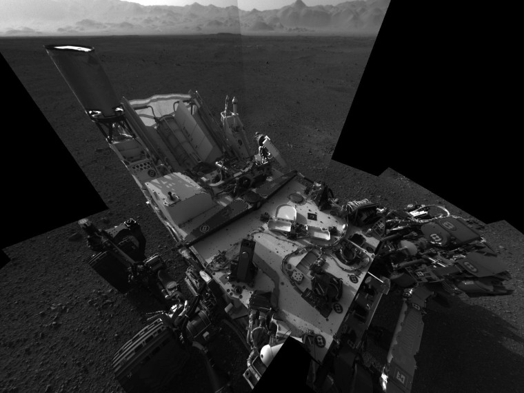 This high-resolution mosaic of 20 images is the first clear self-portrait of NASA's Mars rover Curiosity on the Red Planet. The rear of the rover is at top, with two right-side wheels on the left. The rim of Gale Crater forms the lighter-color strip of the background.
