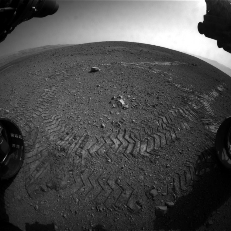 """This image shows the tracks left by NASA's Curiosity rover on Wednesday as it completed its first test drive on Mars. The rover went forward 15 feet (4.5 meters), rotated 120 degrees and then reversed 8.2 feet (2.5 meters). Curiosity is now 20 feet (6 meters) from its landing site, dubbed """"Bradbury Landing."""""""
