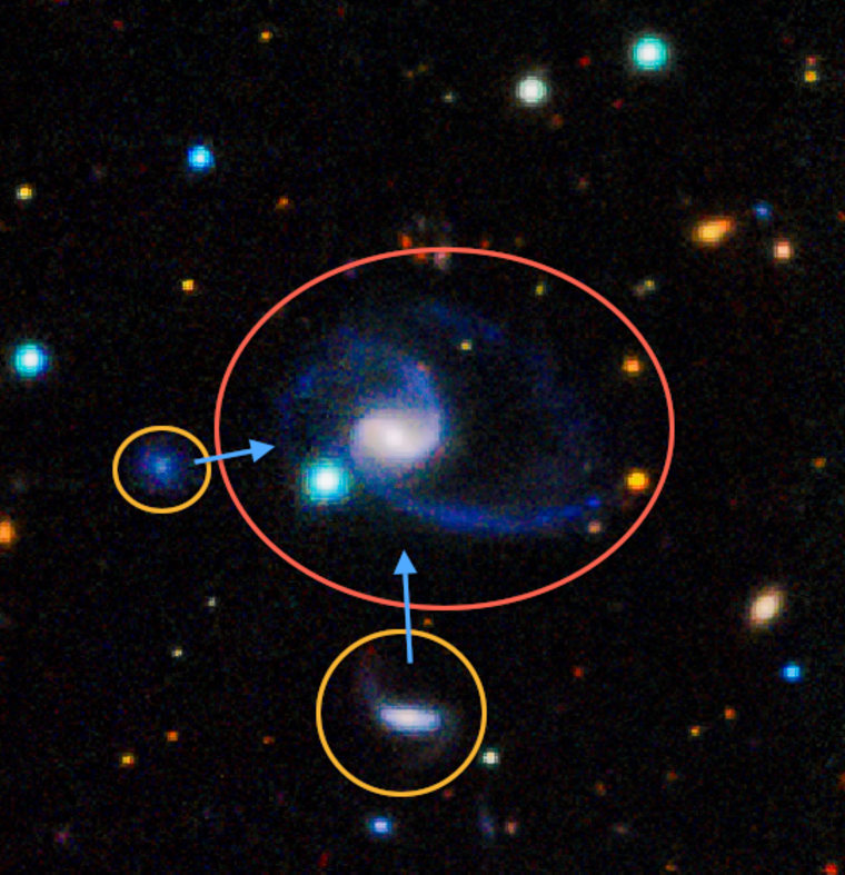 "This image shows one of two ""exact matches"" to the Milky Way galaxy found recently. The larger galaxy, GAMA202627, clearly has two large companions off to the bottom left. In the image, bluer colors indicate hotter, younger stars, like many of those that are found in our galaxy."