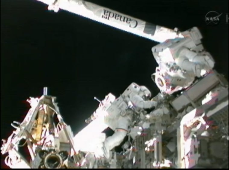 Astronauts prepare space station's robotic arm during spacewalk