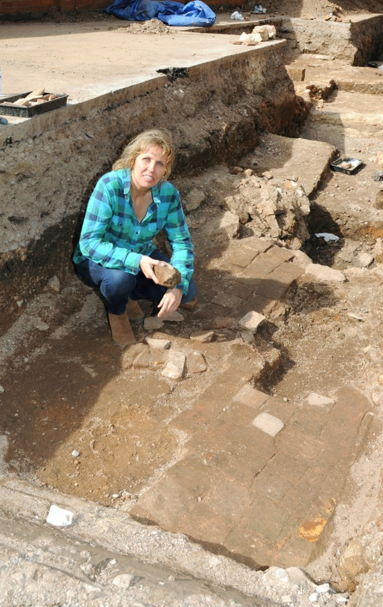 Richard III society member Philippa Langley crouches amid paving stones that may belong to a 17th-century garden containing a memorial to the lost king.