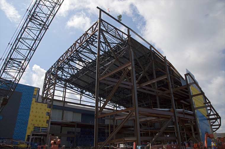 "A steel beam, temporarily ""topped out"" with a tree, was fitted on Wednesday to the highest point of the exhibit facility for space shuttle Atlantis at the Kennedy Space Center Visitor Complex in Florida."