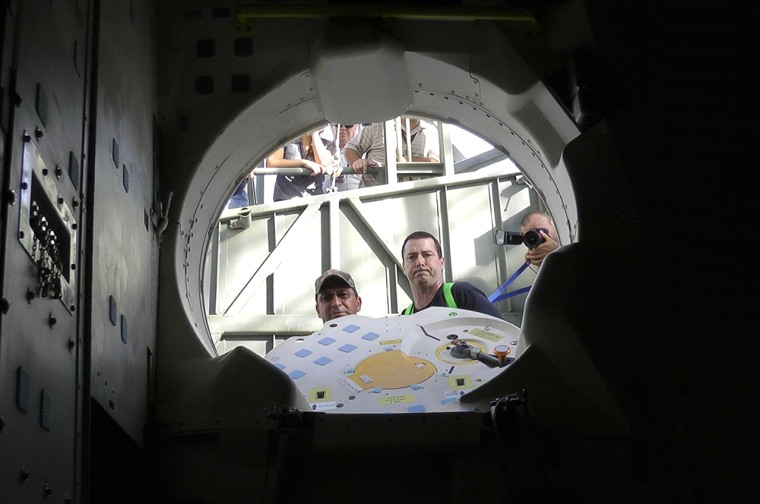 Patch-eye view: NASA techs look into space shuttle Endeavour's crew cabin after storing patches and a photo on board for the orbiter's final ferry flight.