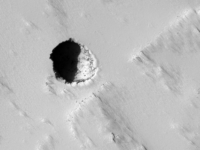 NASA's Mars Reconnaissance Orbiter took this photo of a cave skylight on the southeastern flank of Pavonis Mons, a large volcano in Mars' Tharsis Region. The pit is about 180 meters wide.