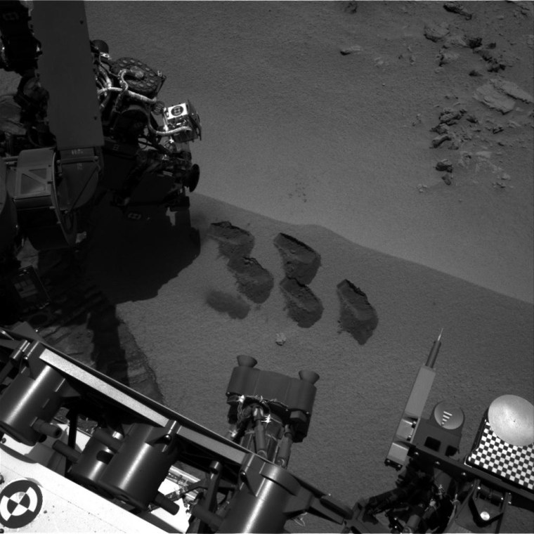 """Bite-marks on Mars. NASA's Mars rover Curiosity used a mechanism on its robotic arm to dig up five scoopfuls of material from a patch of dusty sand called """"Rocknest."""" Each of the pits is about 2 inches (5 centimeters) wide. A sample from that fifth scoop was analyzed by Curiosity's Sample Analysis at Mars (SAM) instruments inside the rover. A second sample from the same scoopful of material was delivered to SAM for analysis on Sol 96 (Nov. 12)."""