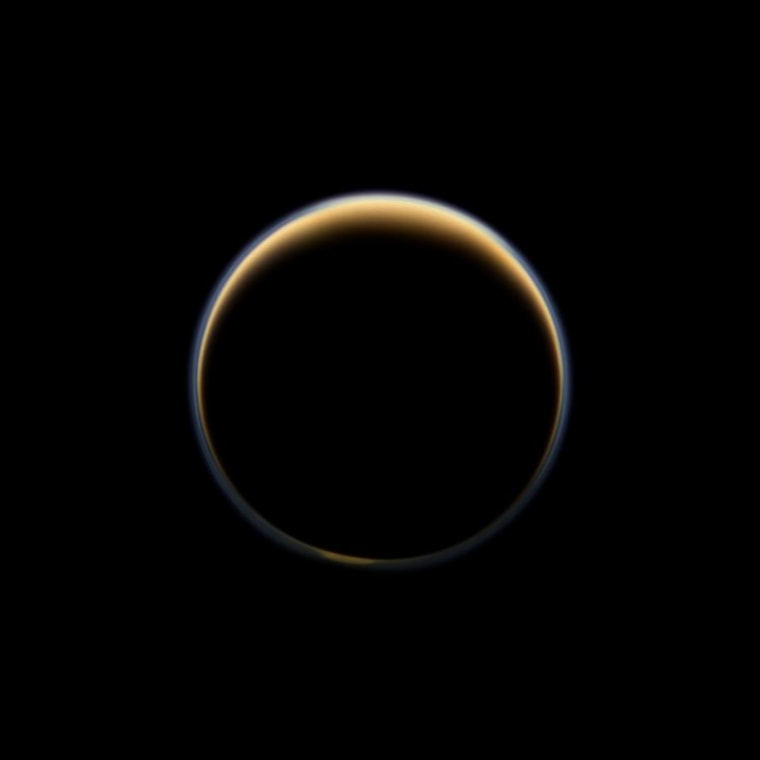 This night-side photo of Titan taken by the Cassini spacecraft shows a buildup of haze over the Saturn moon's south pole (bottom). New results from Cassini's infrared spectrometer show that air is now sinking at the south pole, leading to increased temperatures at high altitude and a large enrichment in trace gases.