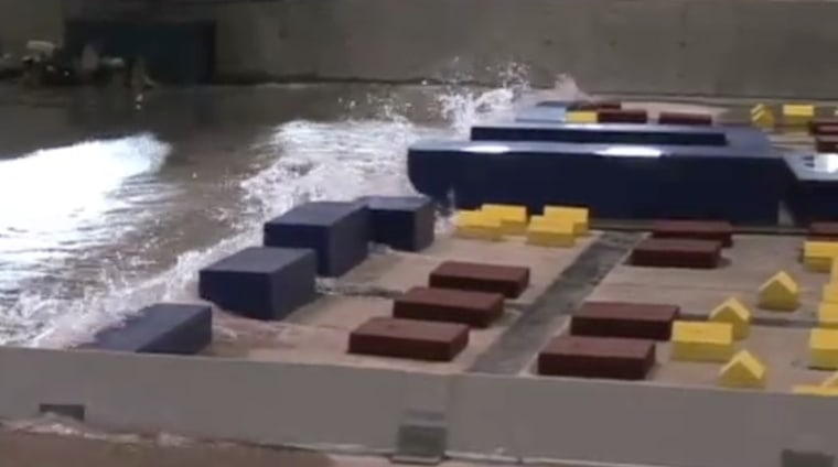 A still image from a video of a scaled-down simulation of a tsunami hitting a coastal Oregon city.