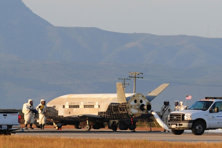 Technicians inspect the military X37-B space plane after its June 2012 landing, which completed the vehicle's second trip to orbit.