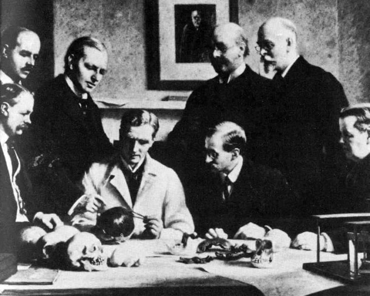 """Who's the hoaxer? This portrait shows many of the major players in the Piltdown """"discovery."""" In the back row: F.O. Barlow, G. Elliot Smith, Charles Dawson, Arthur Smith Woodward. In the front row: A.S. Underwood, Arthur Keith, W.P. Pycraft, and Sir Ray Lankester."""