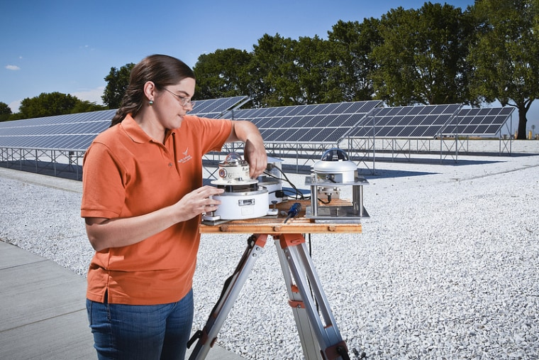 Laura Riihimaki works on an instrument that measures sunlight. Riihimaki is part of a group of researchers working to predict upcoming clouds for solar energy companies.