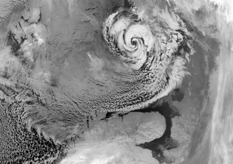 An Arctic hurricane (or polar low) northeast of Scandinavia, with a characteristic eye and counterclockwise swirl of clouds. The gray area in the upper left-hand corner is sea ice.
