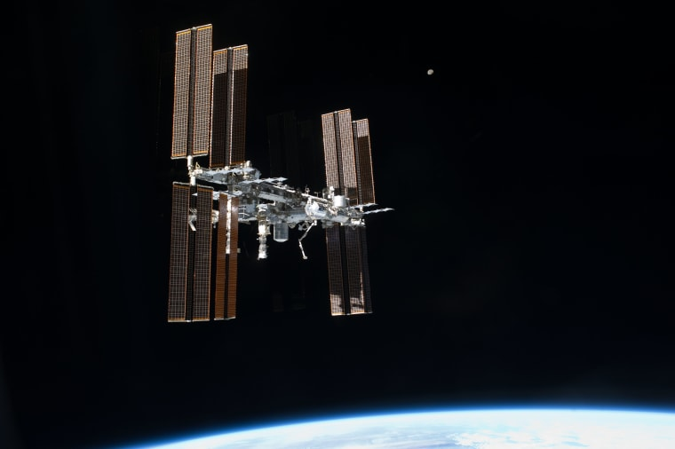 The International Space Station and the moon were photographed from the space shuttle Atlantis just after the two spacecraft undocked on July 19, 2011, during NASA's final shuttle mission STS-135.