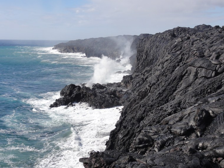 Lava from Kilauea volcano in Hawaii drops into the ocean. Steam plumes rise where the molten rock meets the sea.