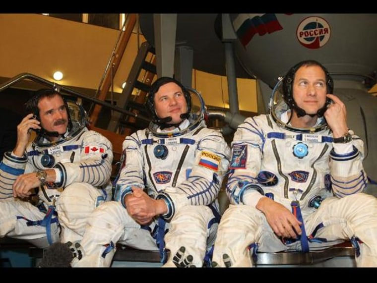Expedition 34 flight engineer Chris Hadfield of the Canadian Space Agency (left), Soyuz Commander Rocan Romanenko (center) and NASA flight engineer Tom Marshburn (right) are scheduled to dock with the International Space Station from the Soyuz TMA-07M spacecraft on Friday morning.