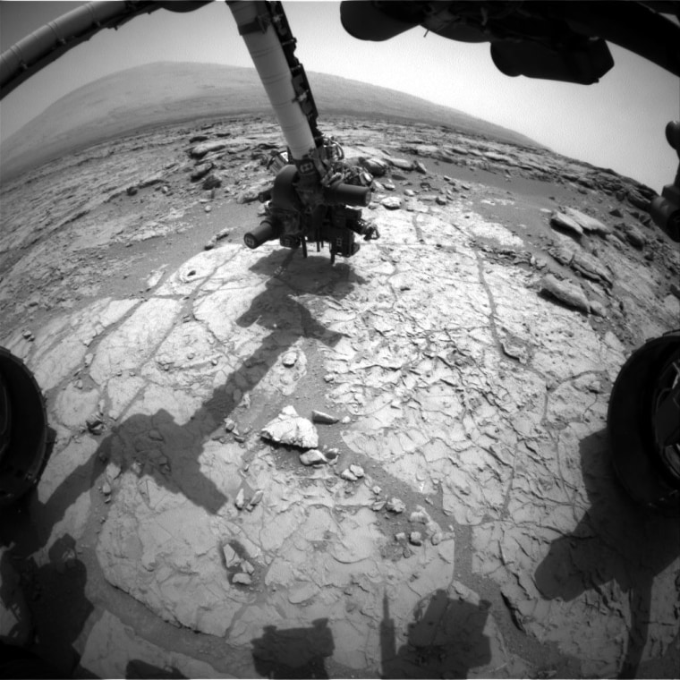 The percussion drill in the turret of tools at the end of the robotic arm of NASA's Mars rover Curiosity has been positioned in contact with the rock surface in this image from the rover's front Hazard-Avoidance Camera (Hazcam). The drill was positioned for pre-load testing, and the Hazcam recorded this image during the 170th Martian day, or sol, of Curiosity's work on Mars Sunday.