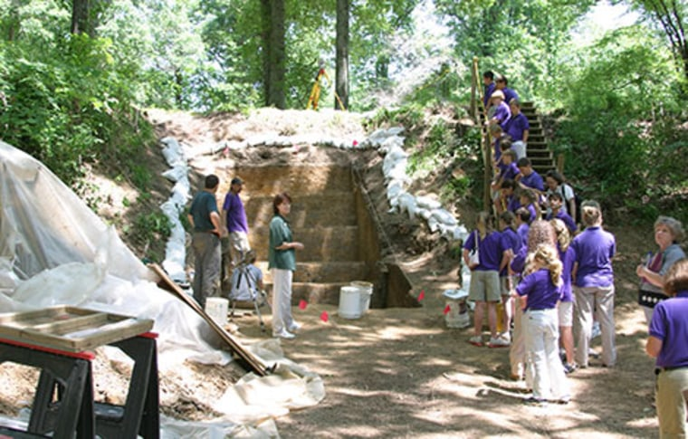 A group of students visits the Washington University excavations of Mound A at Poverty Point.