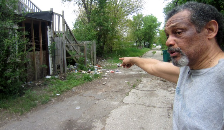 Arthur Joe points to trash spilling into the alley behind his house from abandoned properties in Gary.
