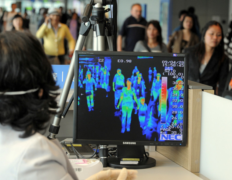 Image: A South Korean quarantine officer monitors a thermal scanner as passengers from an international flight arrive at Incheon airport.