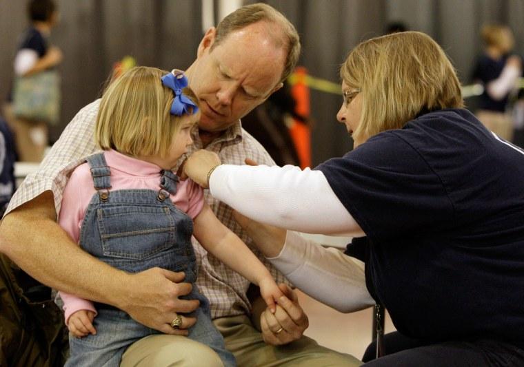 Image: Dan Brundage holds his daughter, Caroline Brundage, as she receives the swine flu vaccine