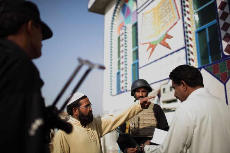 Image: Police officers question a man in front of a mosque