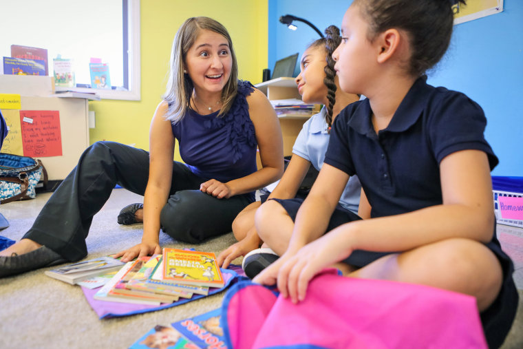 Image: Teacher Karina Flores discusses book selections with Jinnette Santana and Amy Monroy, right, during a reading workshop at The Learning Community charter school in Central Falls, R.I.