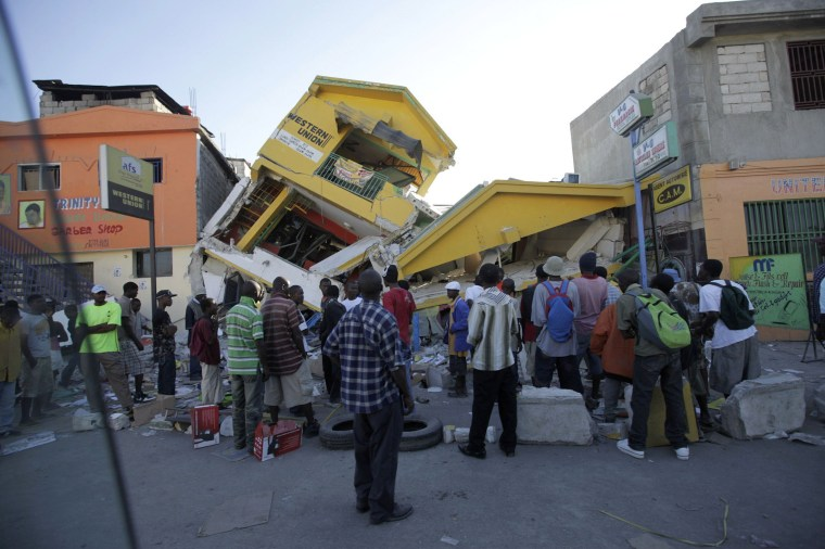 Image: People look at a destroyed building in Port-au-Prince
