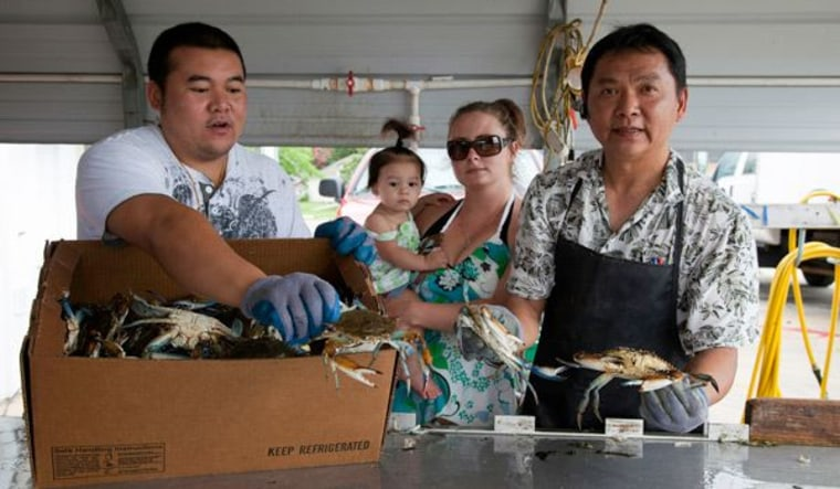 Sananikone, right, is owner of Never Enough Seafood, a blue-crab wholesaler in Lockport, La. A native of Laos, he runs the business with his wife and sons Shawn, 28, left, Tom, and Albert.