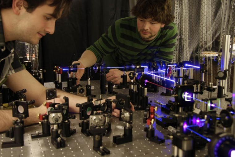 Univ. of Toronto's Dylan Mahler (l) and Lee Rozema (r) prepare pairs of entangled photons to study the disturbance caused by measuring them. Their work suggests some measurements don't wreak so much havoc on a quantum system.