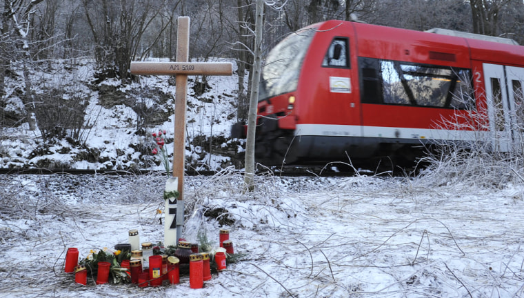 Image: A cross, flowers and candles have been placed close to the place in Blaubeuren-Weiler, Germany, where German entrepreneur Adolf Merckle committed suicide