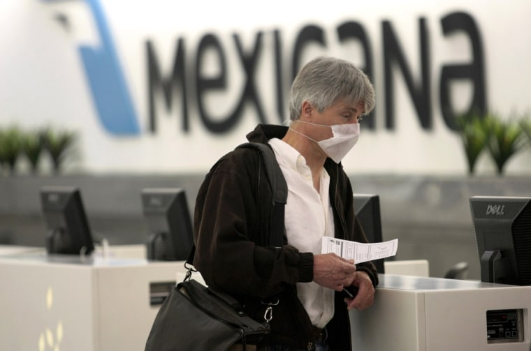 Image: A passenger wears a surgical mask as he holds a questionnaire for a health survey