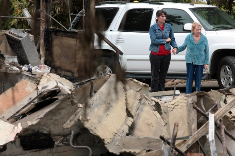 Image: Nanette Pratini, left, and her mother Faye Pratini, 79, hold hands as they return to the rubble of the elder Pratini's home ravaged by a wind-driven wildfire in Santa Barbara, Calif.