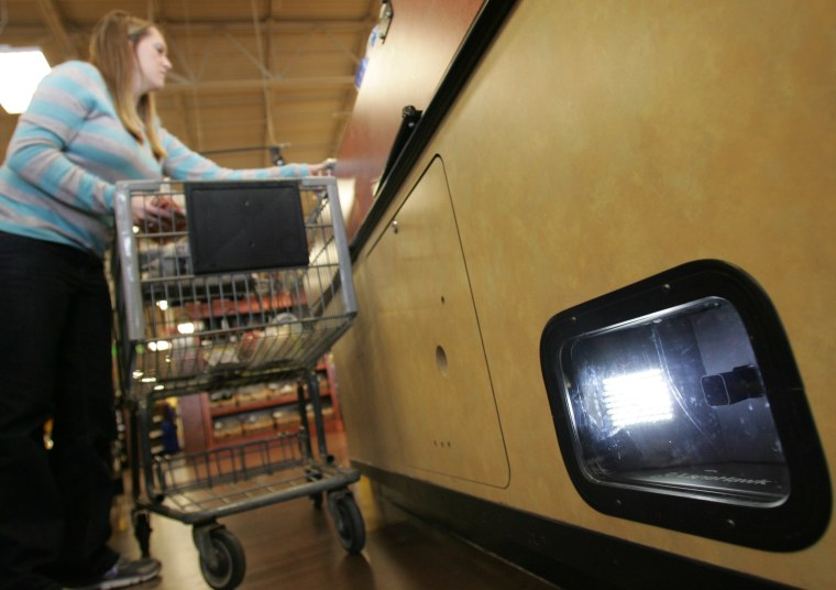 Image: Brooke Zupnick unloads her grocery cart near the LaneHawk loss prevention device at a Kroger store in Gahanna, Ohio