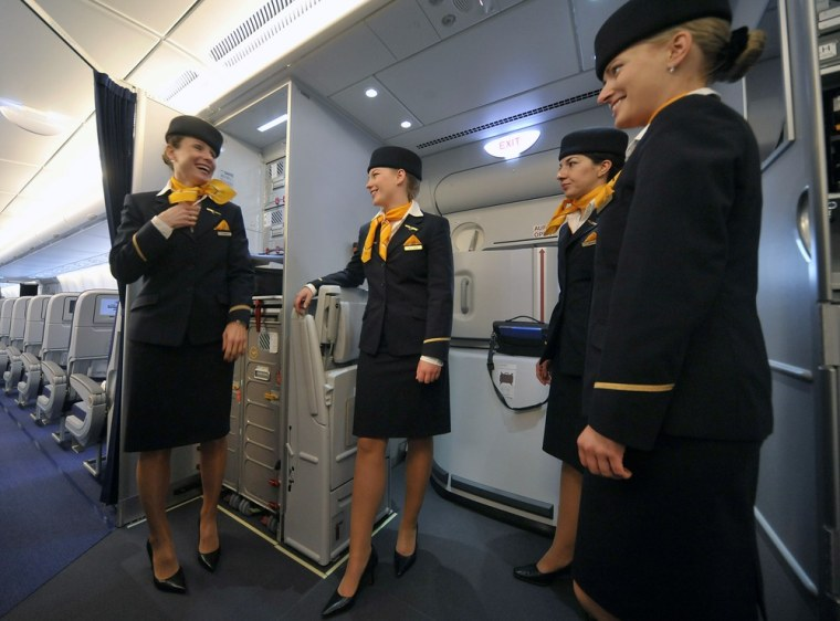 Image: Flight attendants smile as they wait to prepare the cabins in new Airbus A380 aircraft for Lufthansa before hand-over ceremony at manufacturer's site in Finkenwerder, near Hamburg