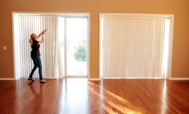 Image: Michelle Carlin opens the blinds on her recently purchased home in Florida