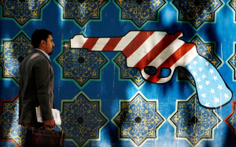Image: An Iranian man walks pass an anti-U.S. graffiti