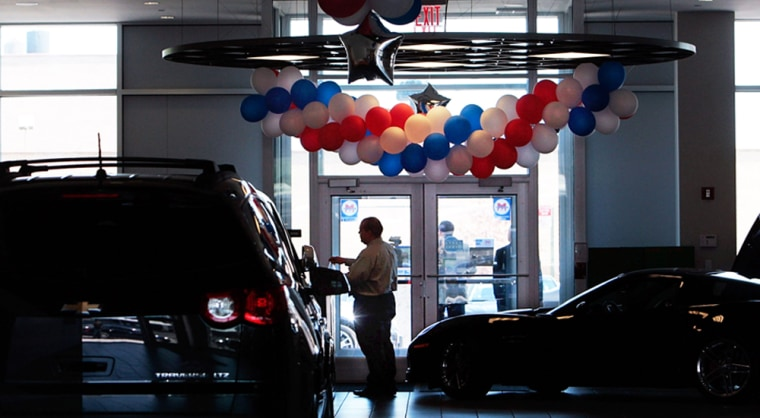 Image: A man stands in the showroom of the Chevrolet-Saturn dealership in New York City in June.