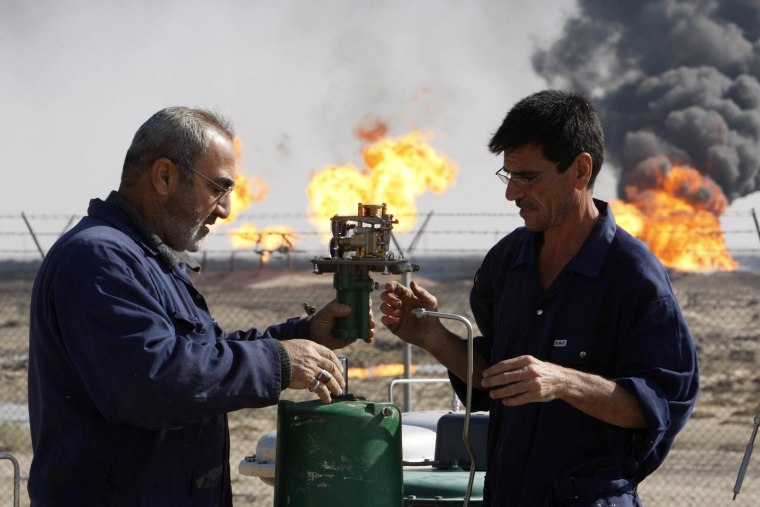 Image: Workers service a gauge at south Rumaila oil field, south of Basra
