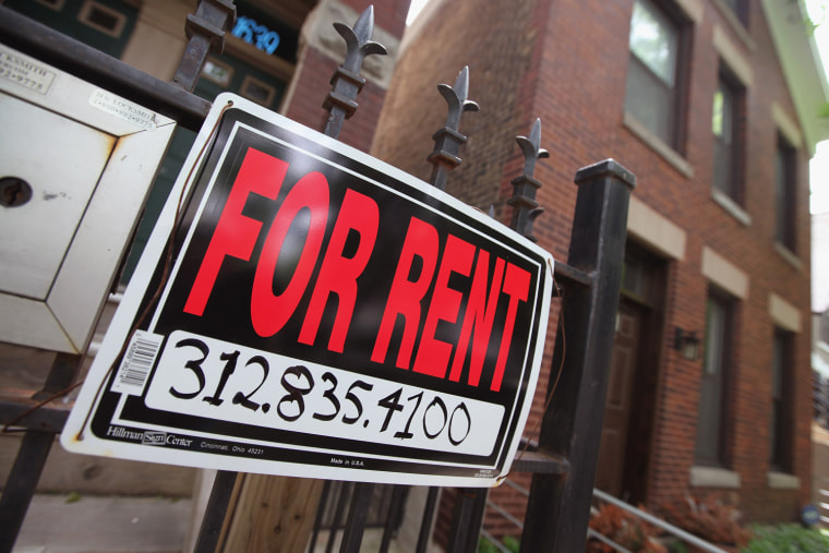 """Image: A """"For Rent"""" sign stands in front of a house"""