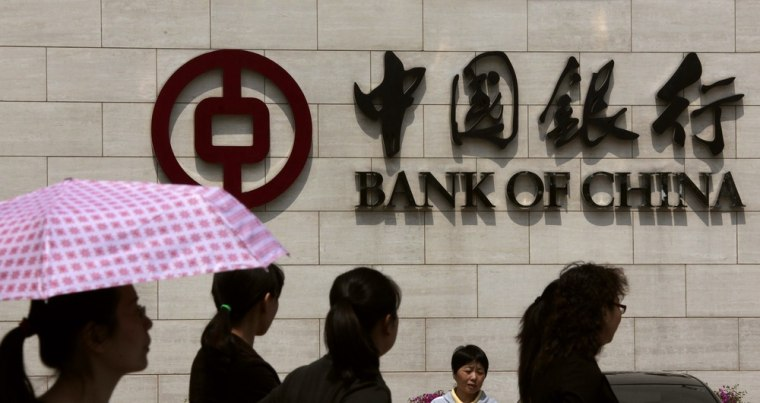 Image: Pedestrians walk past the headquarters of the Bank of China in central Beijing