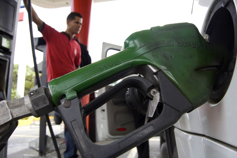Image: An employee fuels up a car in a gas station in Caracas