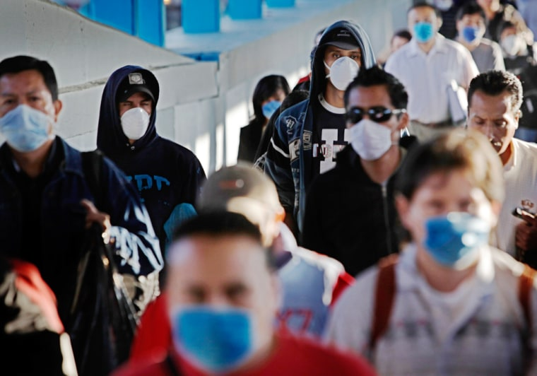 Image:  Passengers wearing face masks as a precaution against swine flu walk inside a metro station in Mexico City